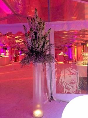 Le bouquet de fleurs blanches est surmonté d'un vase tube en verre et d'une lumière leds blanche dans des billes d'eau en gel.